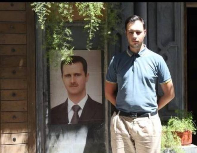 Gauthier Bouchet posant devant un portrait de Bachar El-Assad, à l'été 2011, en Syrie.