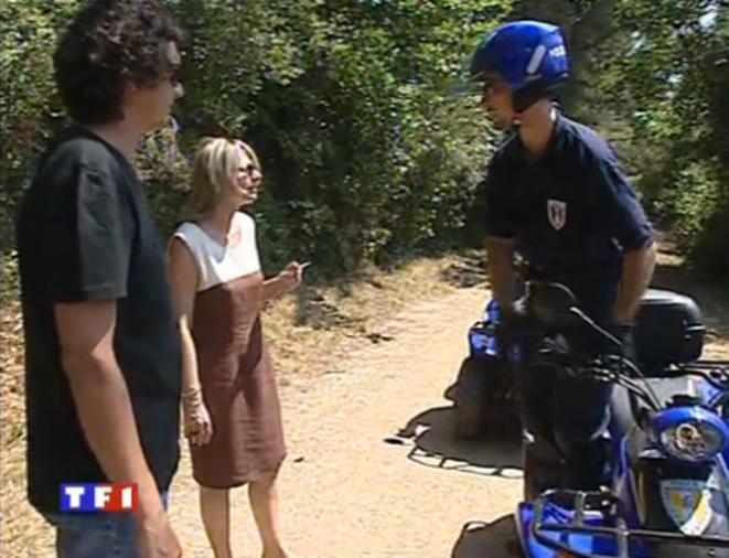 À gauche (en noir, avec des lunettes), un policier municipal joue un promeneur sermonné une cigarette à la main.