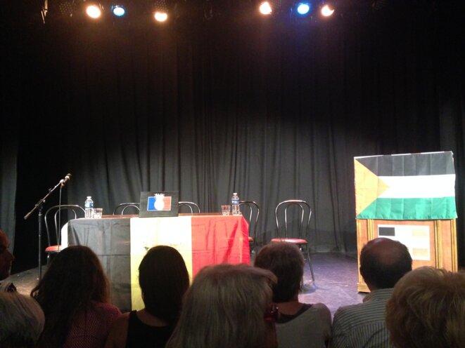 La scène du Théâtre de la Main d'or, avant le début de la conférence. Au centre, un drapeau français orné d'un ananas.