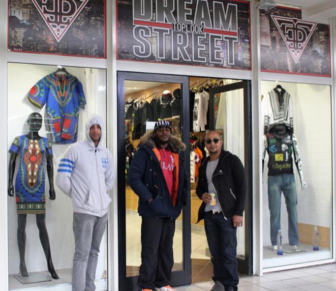 Kevin (au centre) devant sa boutique dans le centre commercial