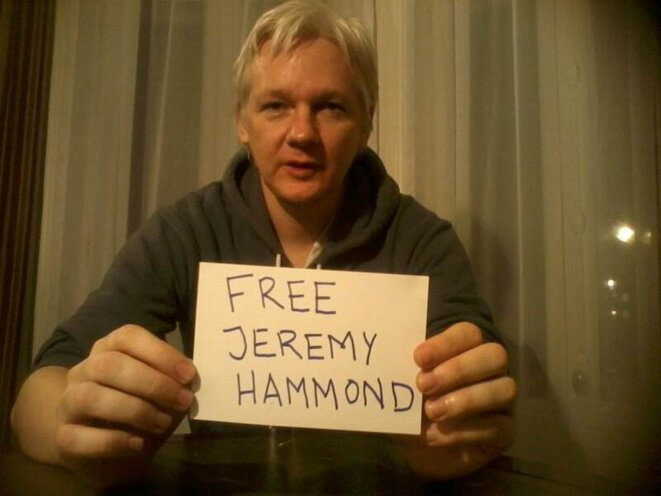"""Julian Assange tenant une pancarte """"libérez Jeremy Hammond"""", en janvier 2013 dans l'ambassade équatorienne à Londres"""