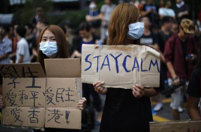 """Des manifestants avec des pancartes """"Restez calmes"""", le 1er octobre"""