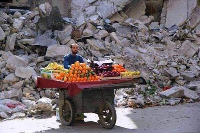 Vendeur de fruit devant un immeuble détruit