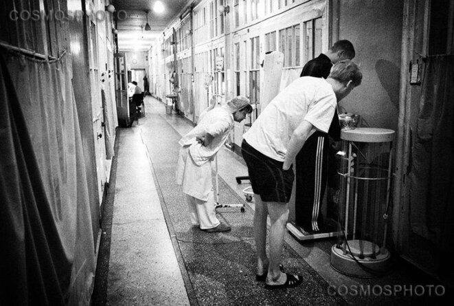 Saint-Pétersbourg. Une infirmière hospitalière vérifie le poids d'un malade pendant qu'un autre patient l'encourage. © Misha Friedman/Cosmos