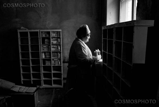 Russie. Une infirmière trie les dossiers des patients morts récemment. © Misha Friedman/Cosmos