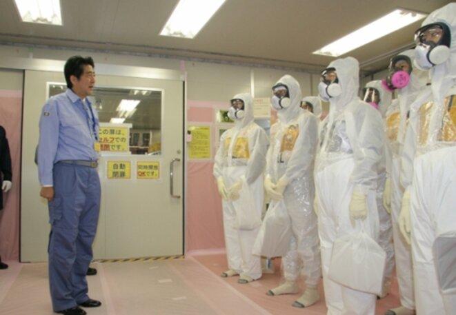 Le premier ministre Shinzo Abe encourage les décontaminateurs de TEPCO, en septembre 2013.