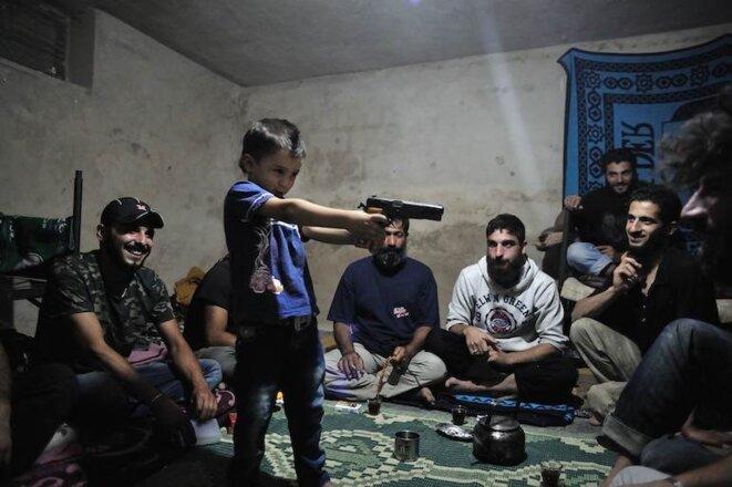 Moment de détente entre compagnons de guerre. Un enfant joue au moudjahidine sous le regard de ses aînés.