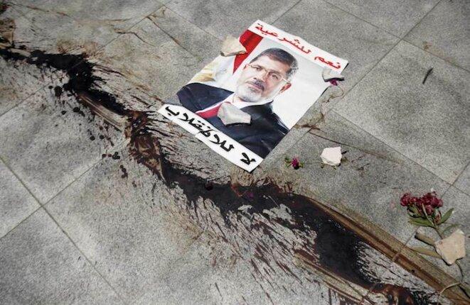 """""""Non au coup d'État, oui à la légitimité!"""" Le sang d'un militant des Frères musulmans coule devant un poster de M. Morsi."""