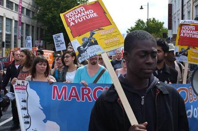 """Une manifestation samedi 13 août. Le manifestant porte un panneau disant """"la jeunesse demande un avenir"""". © Thomas Cantaloube"""