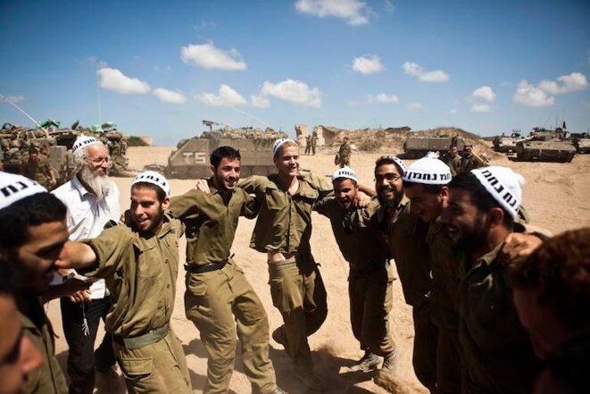 Des soldats israéliens dansent avec les membres d'une secte orthodoxe, devanat Gaza. Juillet 2014. © Nir Elias/Reuters
