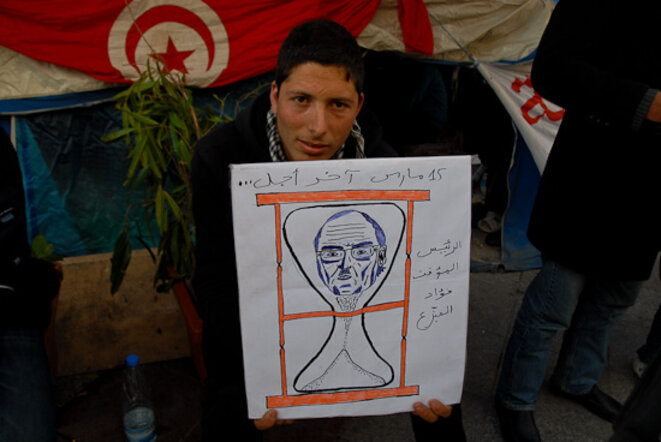 Un manifestant de la place de la Casbah tenant une caricature représentant le président par intérim. © Thomas Cantaloube