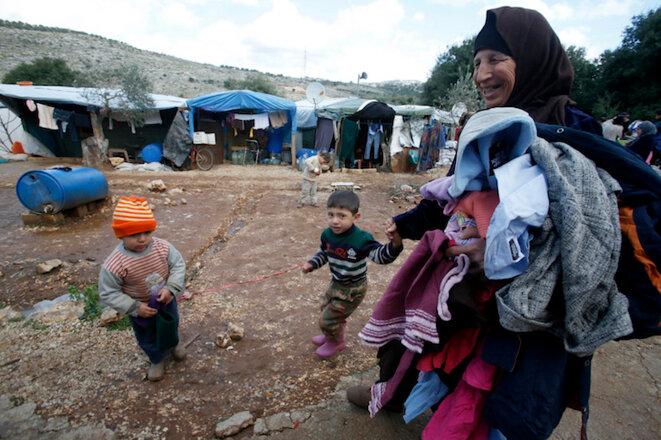 Une famille de réfugiés syriens dans un campement de fortune au sud de Beyrouh © Reuters