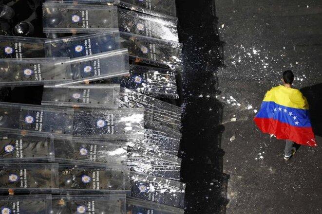Un manifestant défile devant la police anti-émeutes à Caracas, le 12 février 2014