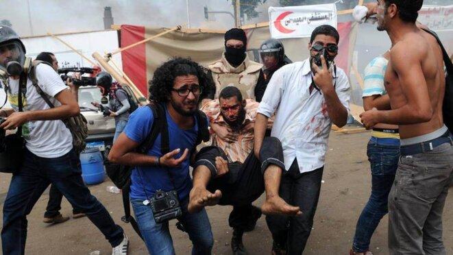 Evacuation dans le sang de la place Ennahda, au Caire © Ahmed Gamal