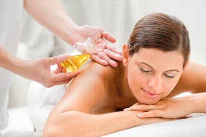 Une femme se fait masser avec de l'huile de pépins de raisin © photographe