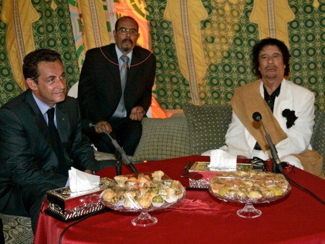 De gauche à droite : Nicolas Sarkozy, le diplomate Moftah Missouri et Mouammar Kadhafi, le 6 octobre 2005. © Reuters