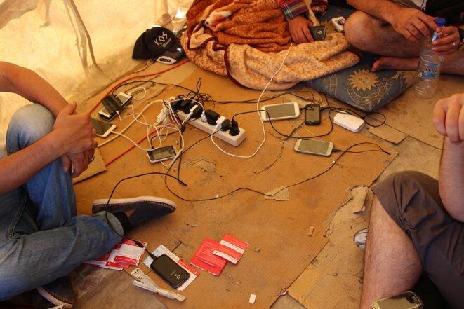 Les réfugiés rechargent leurs téléphones sous la tente