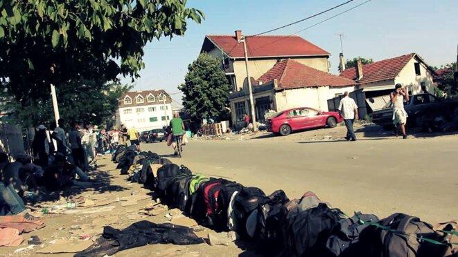 File d'attente de sacs à dos devant le camp