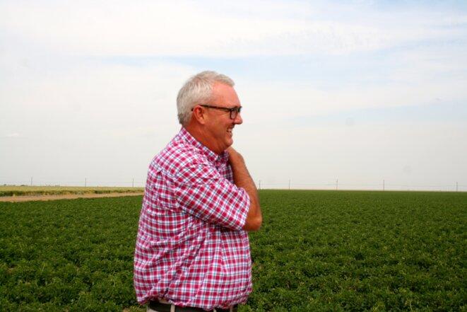 Jim Beecher, devant un champ de tomates.