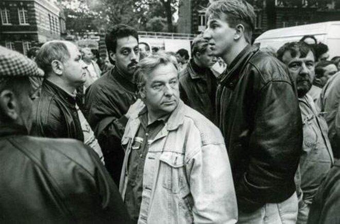 À Valenciennes (59), à la fin des années 1990. Ces salariés sont en colère. Alors qu'ils défendaient les emplois, dans cette région sinistrée, au cours d'une manifestation, un de leur camarade de la CGT a été renversé et tué par un chauffard en 4X4. La colère, plus que la douleur et la tristesse, se lit sur ces visages, dans ces regrds perdus lors de l'hommage qu'ils rendent à leur ami et à sa famille. © Olivier Perriraz