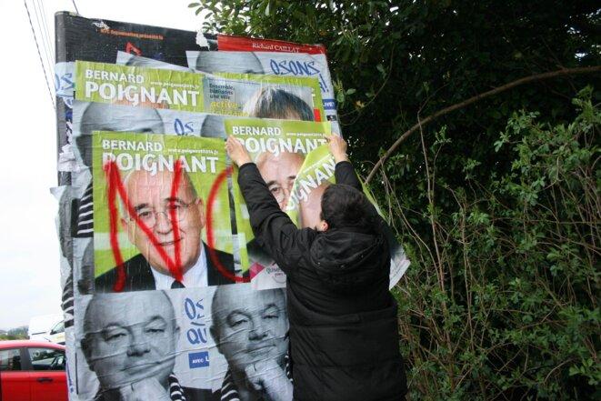 Un militant socialiste en collage, mardi 18 mars © L.B.