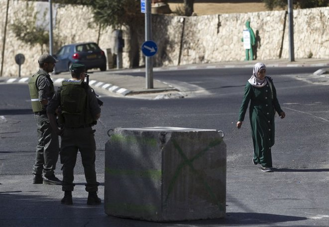 A Palestinian (R) walks past Israeli paramilitary border police at a roadblock in East Jerusalem October 15, 2015. Israel set up roadblocks in Palestinian neighbourhoods in East Jerusalem and deployed soldiers across the country on Wednesday in an effort to stop a wave of Palestinian knife attacks. REUTERS/Ronen Zvulun © Reuters