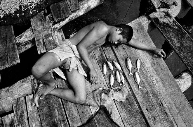 Dans le détroit de Malacca (Indonésie), 2001. Sularso, enfant pêcheur, travaille sur une plateforme à 16 kilomètres des côtes.  © Francesco Zizola / Noor.