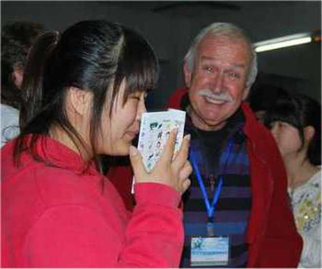 """Edmond donne un """"poŝamiko"""" (mini lexique illustré) à une jeune Asiatique © edukado-net"""