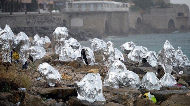 Des migrants se protègent de la pluie sous leur couverture de survie à la frontière italo-française