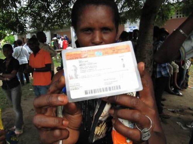 Un électeur brandit sa carte électorale © MM