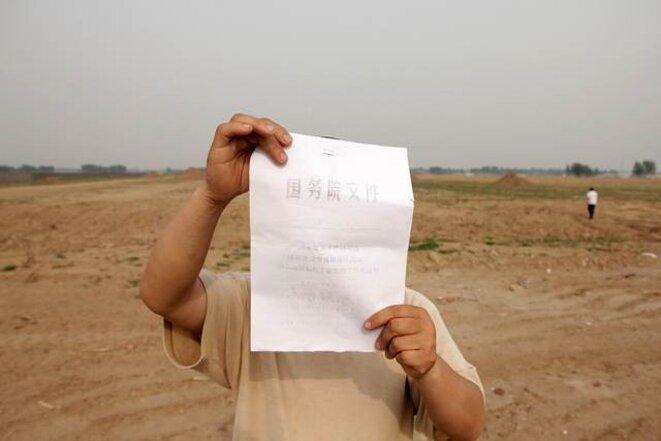 """Ce paysan cache son visage devant la photocopie d'un texte du """"Conseil d'Etat"""" censé protéger les terres cultivables."""