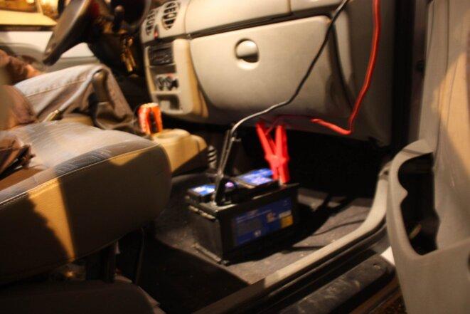 La batterie de sa voiture charge celle du camion où habite André S. © E. Berthaud.