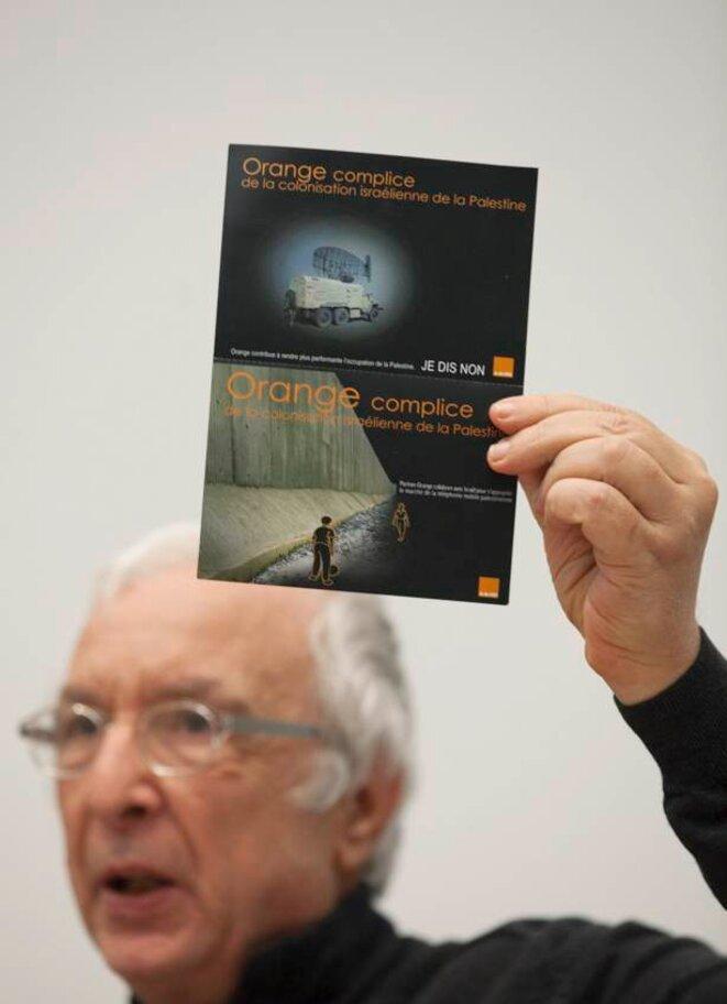 Robert Kissous de l'AFPS montre la carte de la campagne pour dénoncer la complicité d'Orange dans les territoires occupés. © Thomas Haley