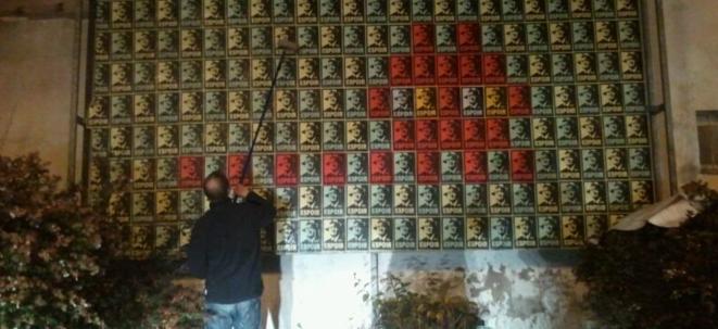 Un militant du Front de Gauche faisant un Space Invader avec des portraits de Mélenchon en mode Shepard Fairey / Obama