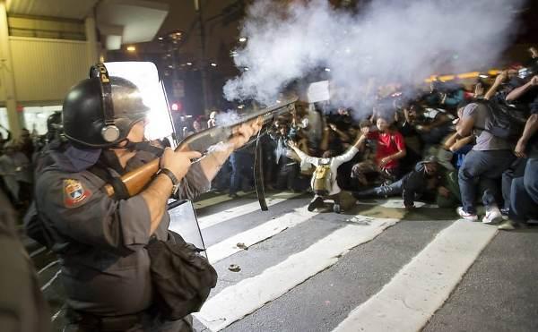 Un policier tire sur des manifestant.e.s à Sao Paulo, le 13 juin 2013