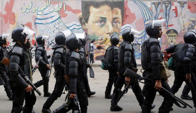 La police égyptienne devant des graffitis anti-militaristes, le 19 novembre 2014.