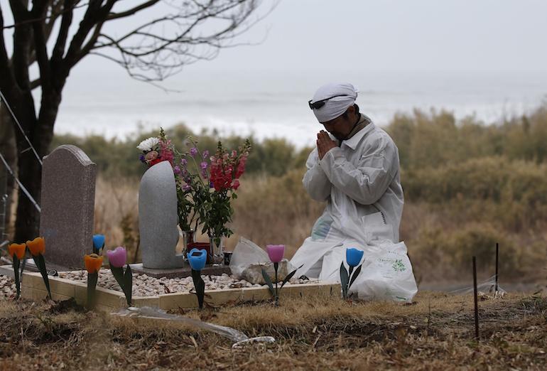 Un réfugié nucléaire prie devant la tombe de sa famille morte durant le tsunami.